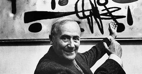 The artist Joan Miró in front of one of his works