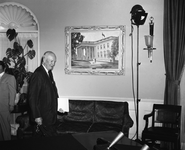 President Dwight D. Eisenhower, walking past Guy Wiggins' painting in the White House